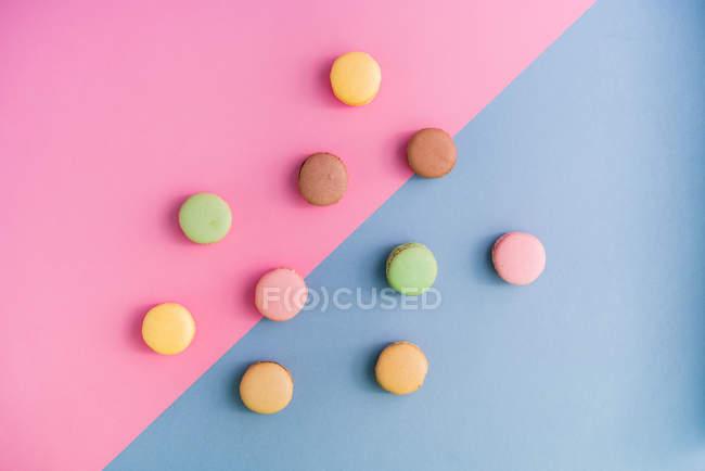 De arriba la colección de brillantes macarones deliciosos sobre fondo rosado y azul. - foto de stock