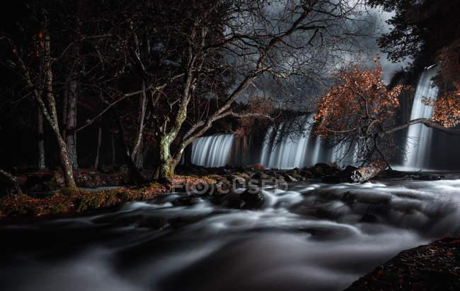 Удивительный водопад в осенних лесах — стоковое фото