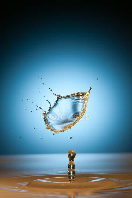 Primo piano colpo di spruzzata di liquido trasparente di colore su sfondo blu — Foto stock