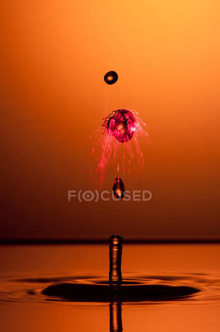 Closeup shot of splash of transparent liquid of color on orange background — Stock Photo