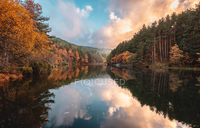 Calm river between autumn forest and hills at sunrise — Stock Photo