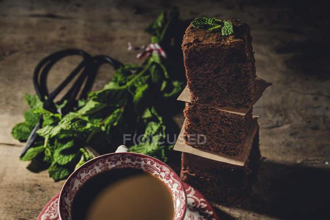 Morceaux empilés de brownie au chocolat avec menthe sur table en bois — Photo de stock