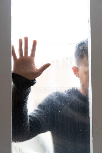 Man behind steamy glass with hand on it — Stock Photo
