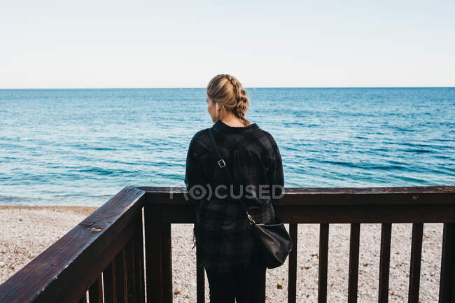 Вид сзади на молодую женщину в повседневной одежде, стоящую рядом с перилами на набережной и любующийся видом на чудесное море в Алтее, Испания — стоковое фото