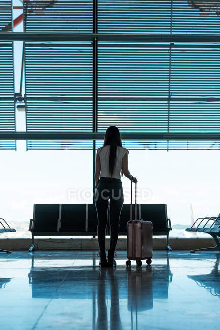Back view lady holding handle of luggage bag near window and bench in waiting room of airport in Porto, Portugal — Stock Photo