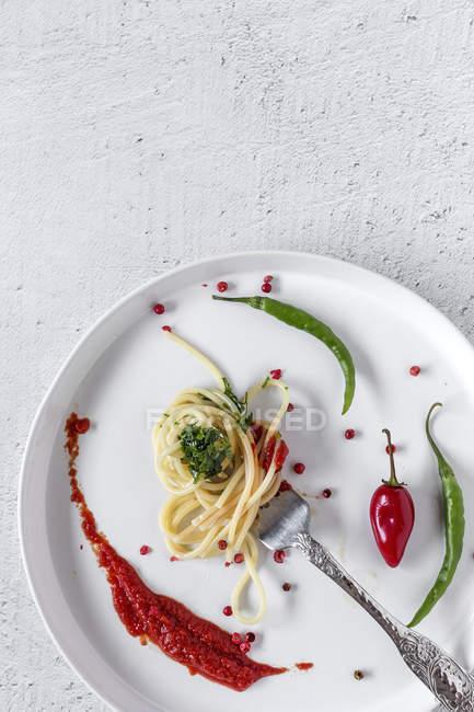 Spaghetti mit Tomatenpesto und Sauce auf Gabel auf weißem Hintergrund — Stockfoto