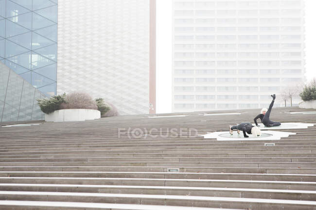 Young women in dark wear doing sport on stairs near modern building in Lithuania — Stock Photo