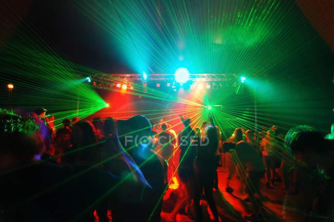 Persone irriconoscibili sulla pista da ballo illuminata — Foto stock