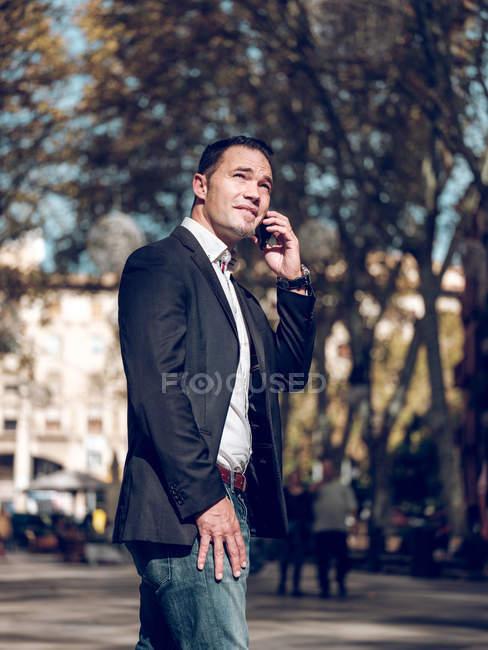 Hombre adulto atractivo en chaqueta elegante manteniendo la mano en el bolsillo y mirando hacia otro lado mientras tiene conversación de teléfono inteligente - foto de stock