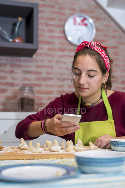 Teenage girl using the smartphone while working on traditional pastry — Stock Photo