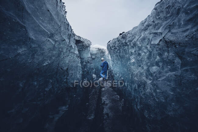 Человек забирается в красивую голубую ледяную пещеру — стоковое фото