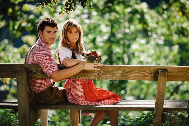 Чоловік і жінка в традиційних австрійських вбрання, дивлячись на камеру, сидячи на дерев'яні лавки на розмитість фону зелений сад — стокове фото
