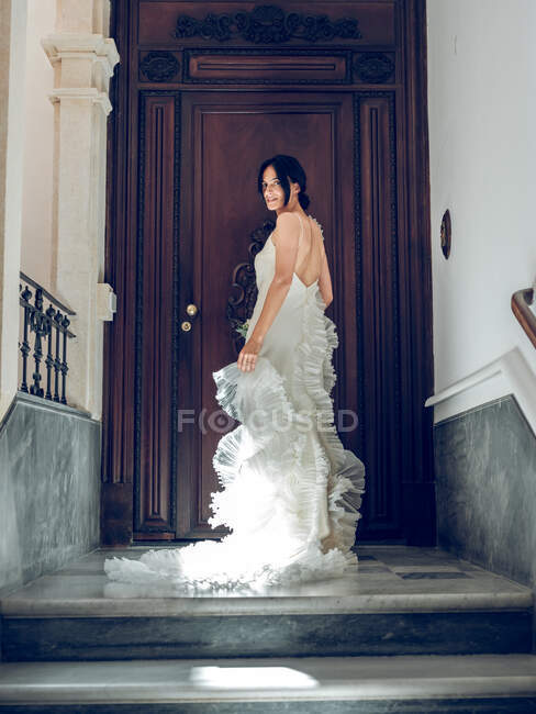 Bride posing on steps for camera — Stock Photo