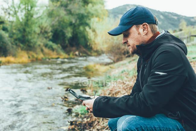 Молодий чоловік тримає компас у горі поруч з річкою з коричневим кольором. — стокове фото