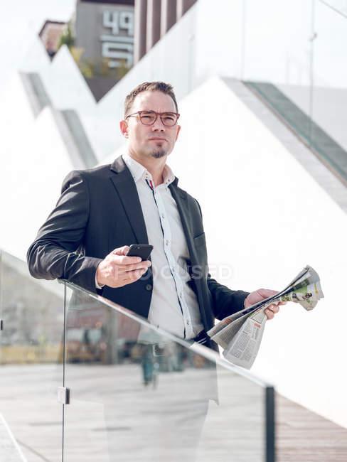 Atractivo hombre adulto en gafas con periódico fresco y el uso de teléfonos inteligentes, mientras que de pie cerca de edificio moderno en la calle de la ciudad - foto de stock