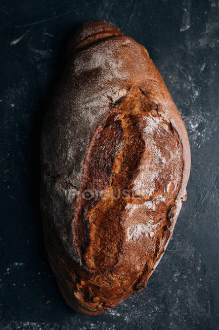 Homemade rustic bread loaf on dark background — Stock Photo