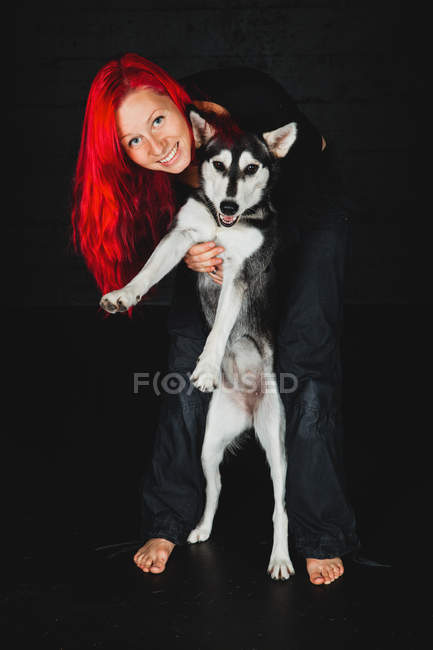 Young woman with bright red hair smiling and looking at camera while hugging puppy of adorable Siberian Husky on black background — Stock Photo