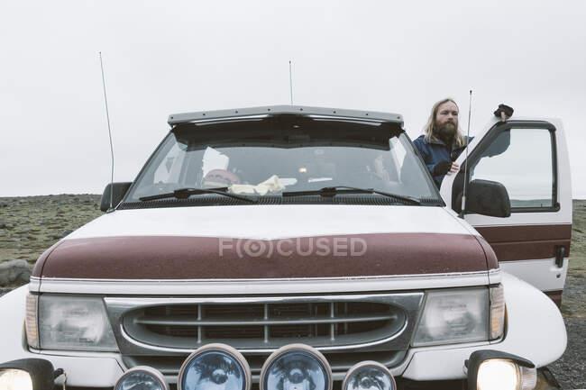 Взрослый бородатый мужчина, стоящий рядом с машиной на отдаленной холодной дороге во время путешествия, Исландия — стоковое фото