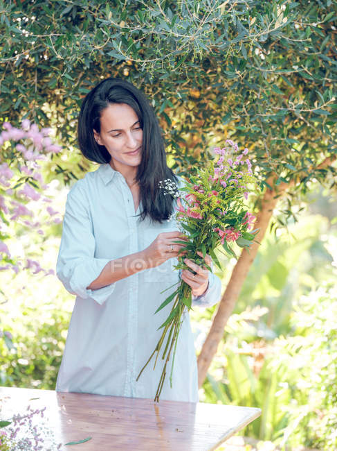 Smiling woman holding bouquet in garden — Stock Photo