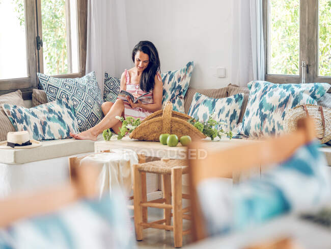 Woman reading magazine on sofa — Stock Photo