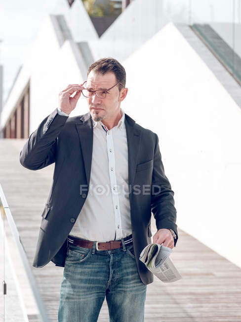 Handsome man in elegant jacket holding fresh newspaper and looking away while standing near modern building on city street — Stock Photo