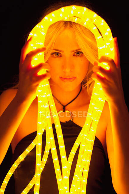 Beautiful young lady holding glowing tubes of neon light and looking at camera in dark room — Stock Photo
