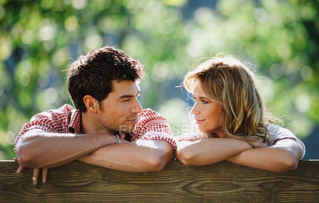Junger Mann und Frau in traditioneller österreichischer Kleidung lehnen sich auf den Rücken einer Bank und schauen einander an, während sie vor verschwommenem Hintergrund des Gartens sitzen — Stockfoto