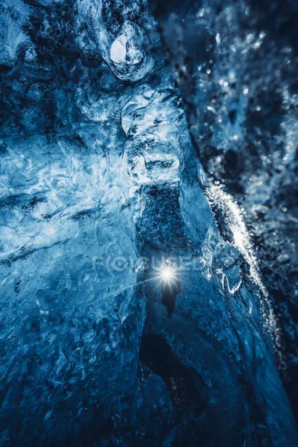 Viajero caminando en la cueva de hielo azul - foto de stock