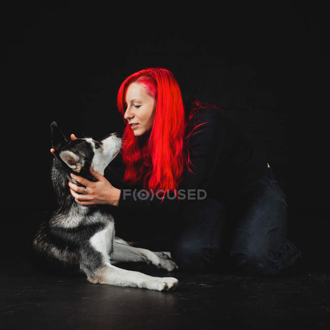 Young woman with bright red hair playing with puppy of adorable Siberian Husky on black background — Stock Photo