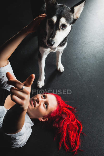 Young woman with bright red hair with puppy of Siberian Husky lying on floor and pointing with finger — Stock Photo