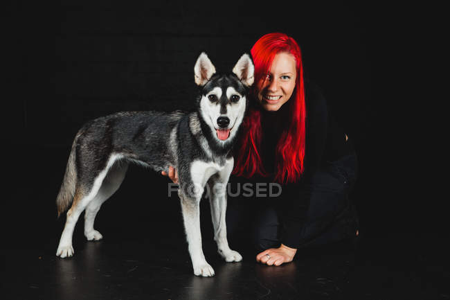 Portrait of young woman with bright red hair with puppy of Siberian Husky on black background — Stock Photo