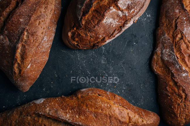Homemade rustic bread loaves on dark background — Stock Photo