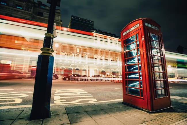 Длительная экспозиция ярких следов света возле красной телефонной будки на ночной улице города — стоковое фото