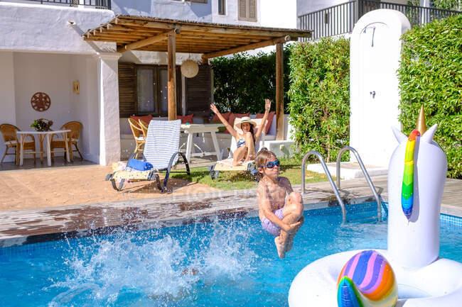 Симпатичный мальчик в плавательных шортах и очках, прыгающий в воду бассейна, проводя время с мамой на курорте — стоковое фото