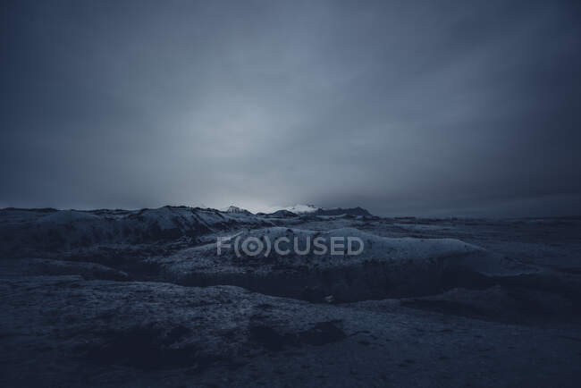 Landscape of tranquil cold snowy terrain with little light in night time, Iceland — Stock Photo