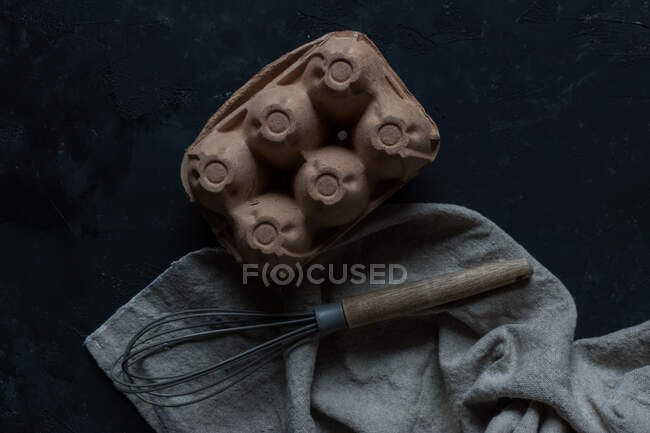 From above shot of old whisk and piece of gray cloth lying near egg carton on black tabletop — Stock Photo