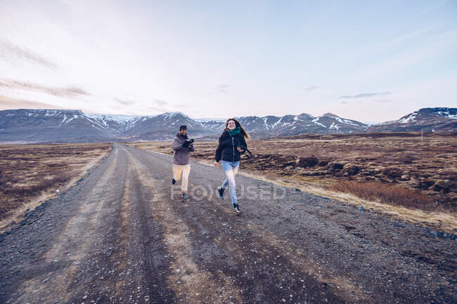 Couple running on road between death lands — Stock Photo