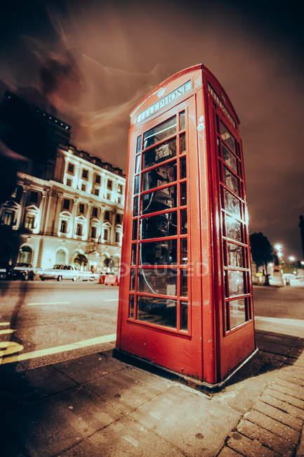 Longa exposição tiro da caixa de telefone na rua da cidade da noite — Fotografia de Stock