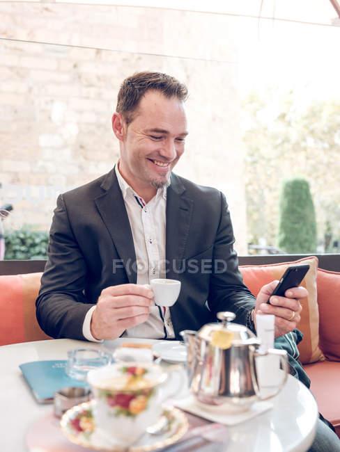 Attrayant homme adulte en veste formelle souriant et tenant tasse de café tout en étant assis à la table de café et smartphone de navigation — Photo de stock