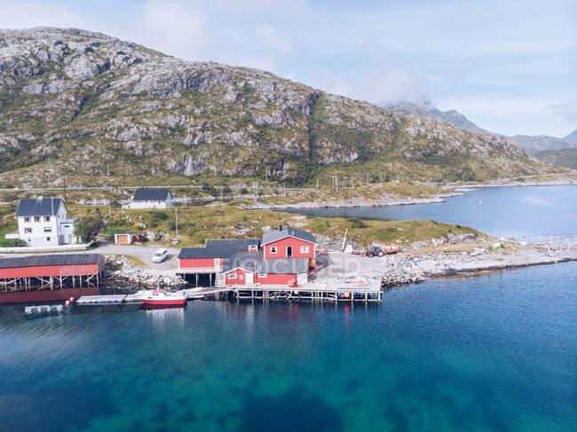 Вид на голубую воду и пристань на скалистом побережье Лофотенских островов под солнечным светом, Норвегия — стоковое фото