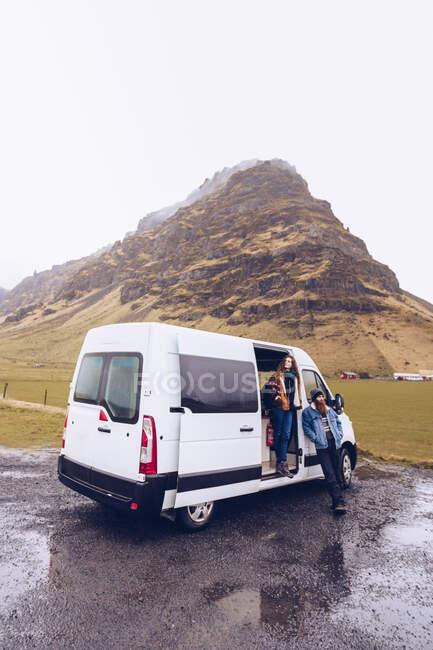 Хлопець і приваблива жінка в теплому одязі з кухлем, що дивиться далеко відкритими дверима фургона біля скелястого пагорба в Ісландії — стокове фото