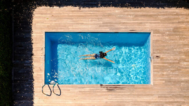 From above shot of unrecognizable female swimming in transparent water of pool while resting in resort — Stock Photo