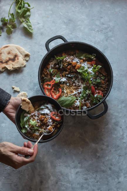 Manos humanas sosteniendo un tazón sobre una olla de ragú con lentejas y curry de batata y un tazón sobre una mesa gris - foto de stock