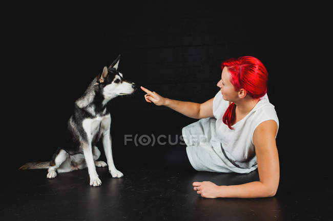 Young woman with bright red hair lying on floor and touching nose of adorable Siberian Husky on black background — Stock Photo