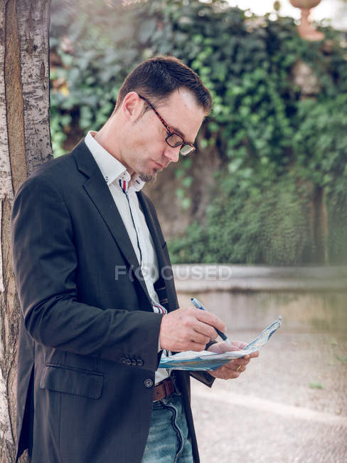 Side view of handsome man in glasses making notes on city map and looking away while leaning on tree near pond — Stock Photo