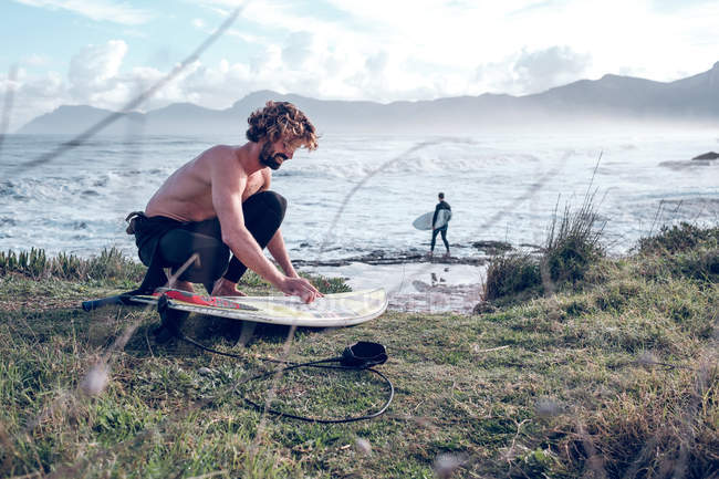 Young man cleaning surfboard on ocean coast — Stock Photo