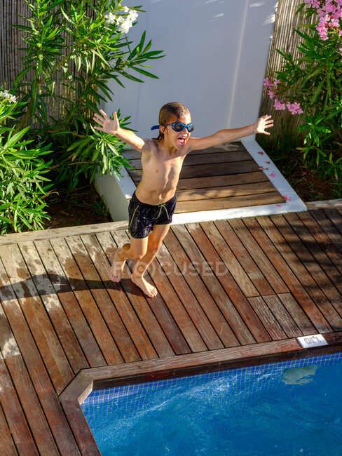 Сверху снимок смешного мальчика в плавательных шортах и очках, бегущего по бассейну к чистой воде и кричащего от волнения — стоковое фото