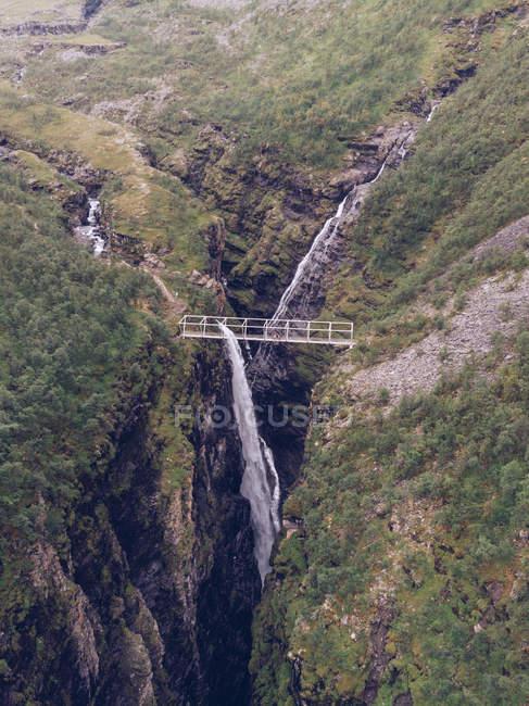 Ponte sobre a ravina espetacular e cachoeira na natureza — Fotografia de Stock