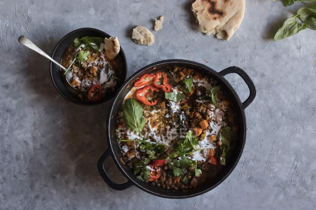Topf Ragout mit Linsen-Süßkartoffel-Curry und Schüssel auf grauer Tischplatte — Stockfoto