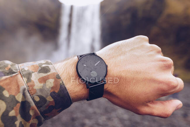 Рука парня, показывающего черные часы возле каскада воды в Исландии на размытом фоне — стоковое фото
